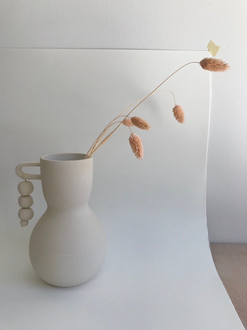 White clay vase with handle and hanging beads, botanical stems inside.