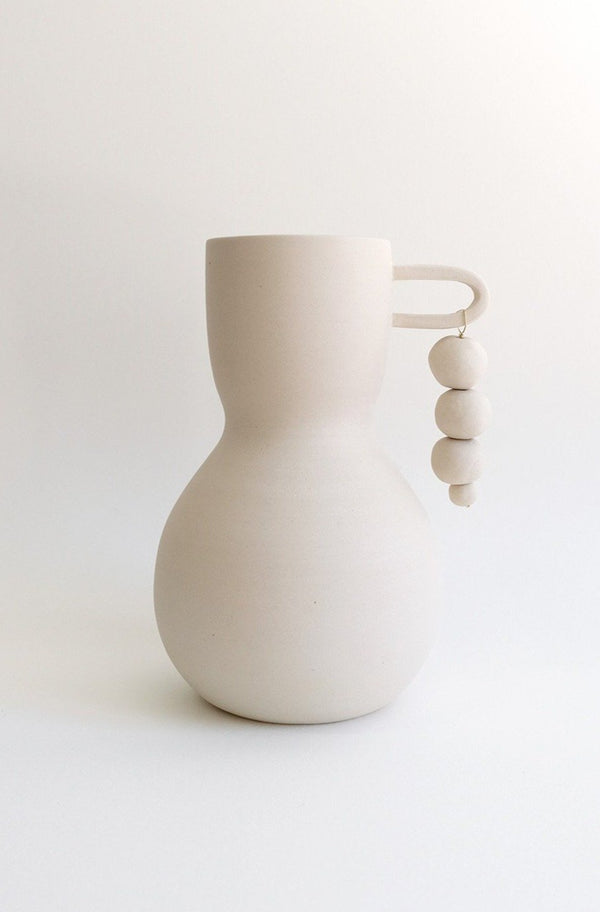 White clay vase with handle and hanging beads.