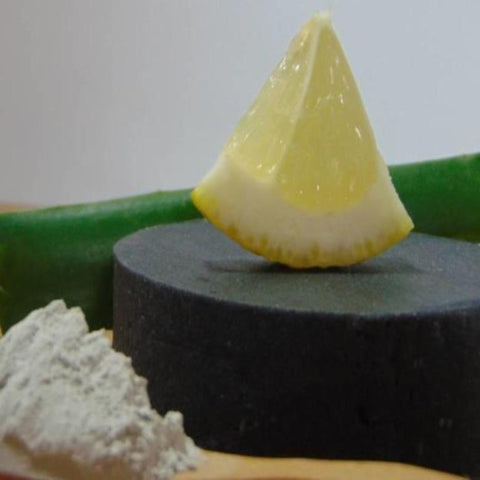 Beauty by Francesca Activated Charcoal Face and Body Soap displayed with lemon and clay