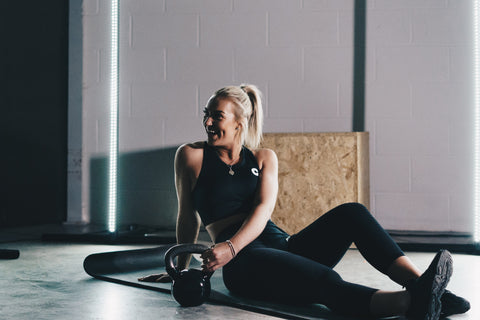 a gym woman sitting in her gym kit