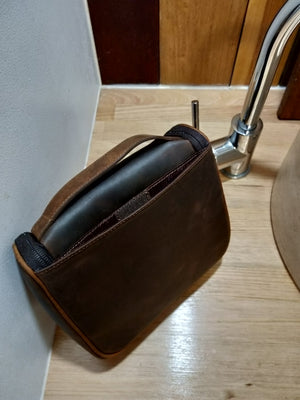 Toiletry bag in chocolate leather with a tan leather handle