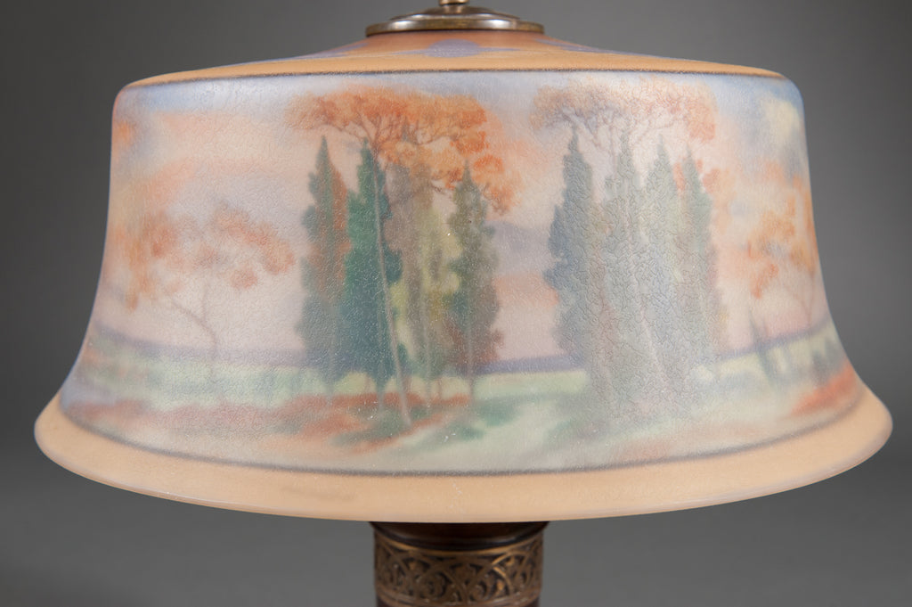 A Reverse Painted Pairpoint Landscape Lamp with Carved Wooden Base