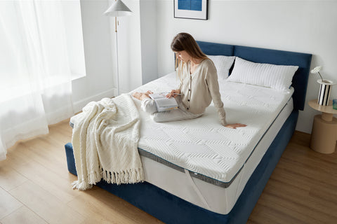 Woman reading book on top of Bedsure hybrid memory foam mattress topper with bamboo charcoal
