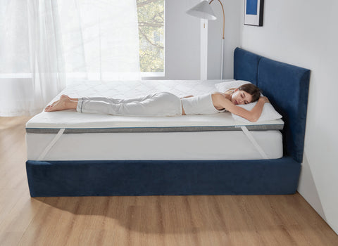 Woman sleeping face down on Bedsure memory foam mattress topper with bamboo charcoal