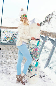 girl wearing bright blue leggings and white knit sweater with snowboard in hand in front of snowy mountains. White beanie