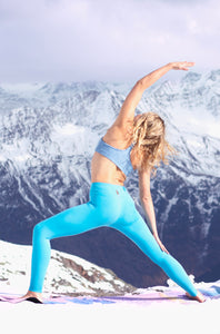girl doing reversed warrior yoga pose in front of snowy mountains in turqoise leggings and sports bra