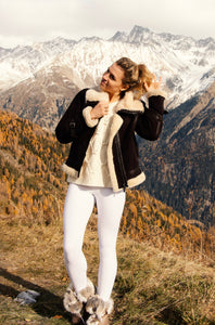blonde girl wearing white leggings, white knit pullover and a motorcycle jacket in front of snow mountains