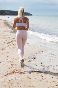 girl running along the beach in natural leggings