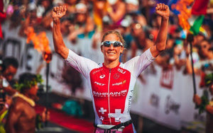 female triathlete raises hands finish line