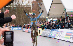 Muddy bicycle racer raises arms in victory