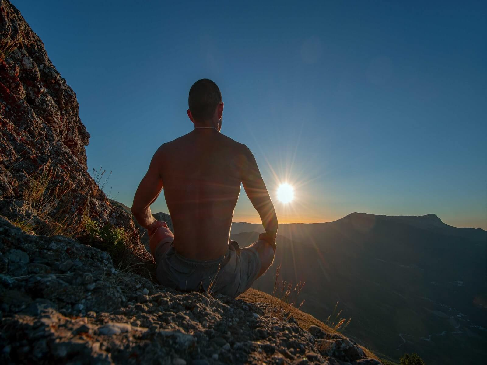 man meditating on a mountain