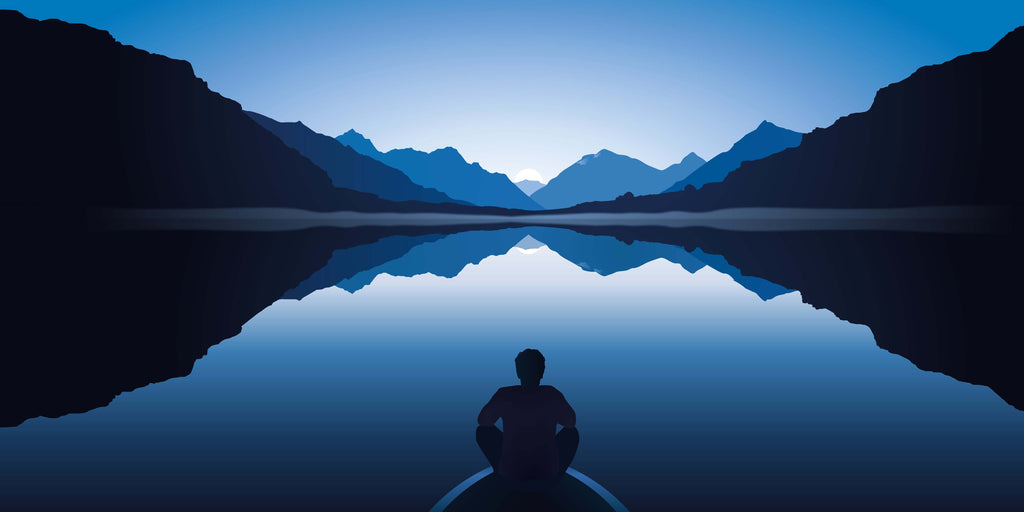 man meditating in front of an ocean