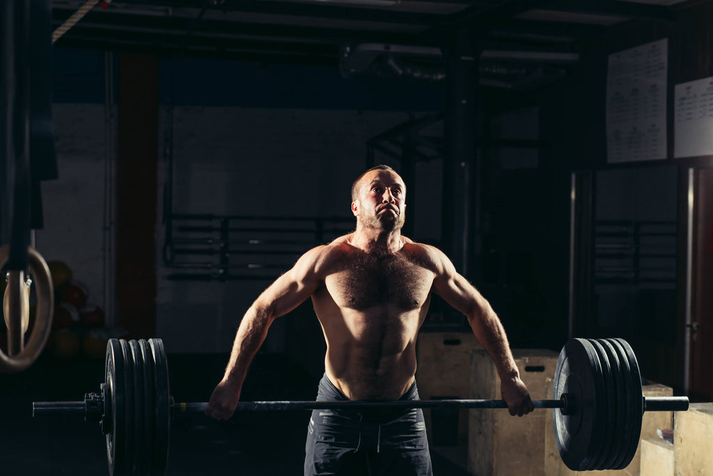 man lifting weights showing how cbd helps muscle recovery