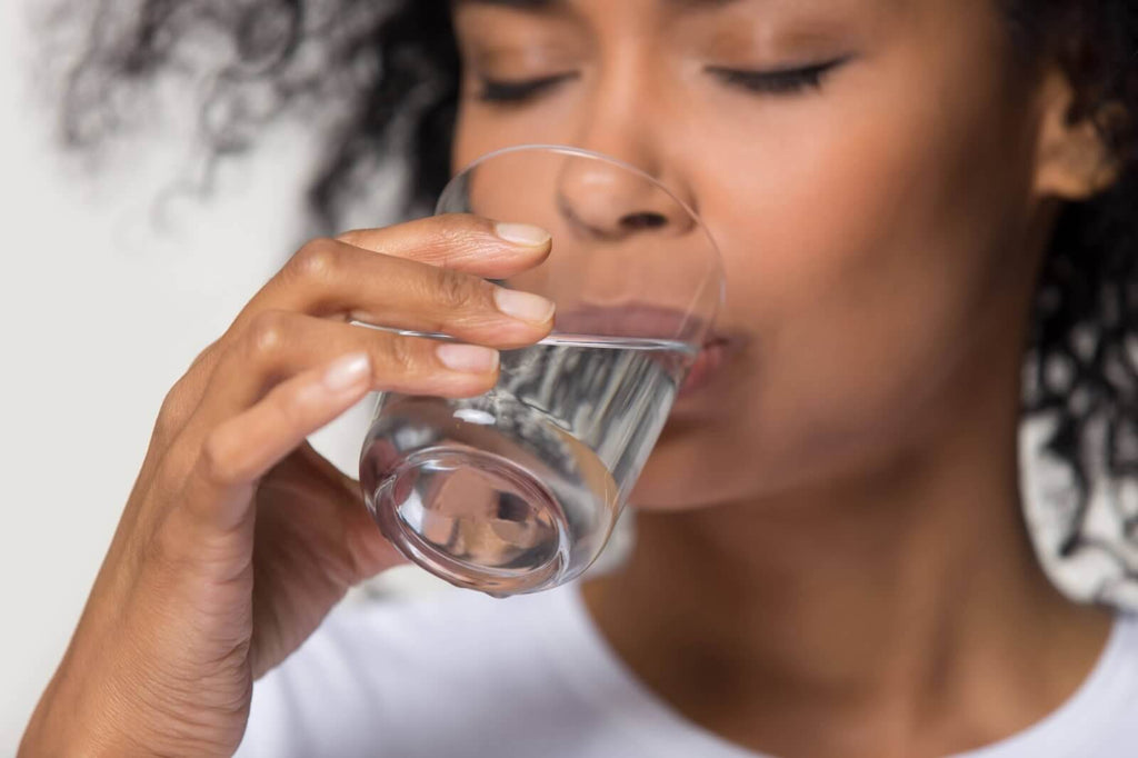 woman drinking water to treat a hangover