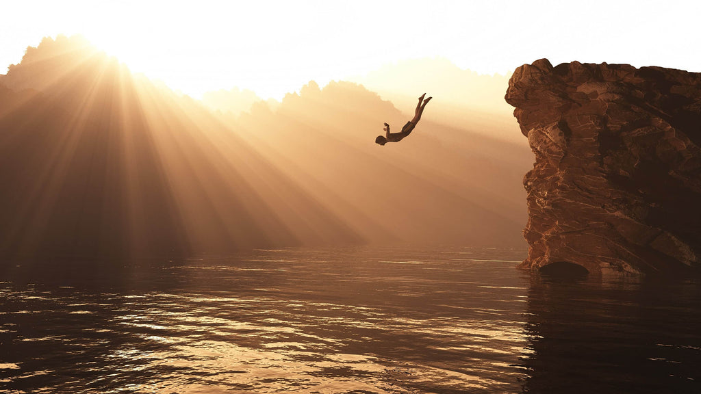 man jumping off a cliff into water