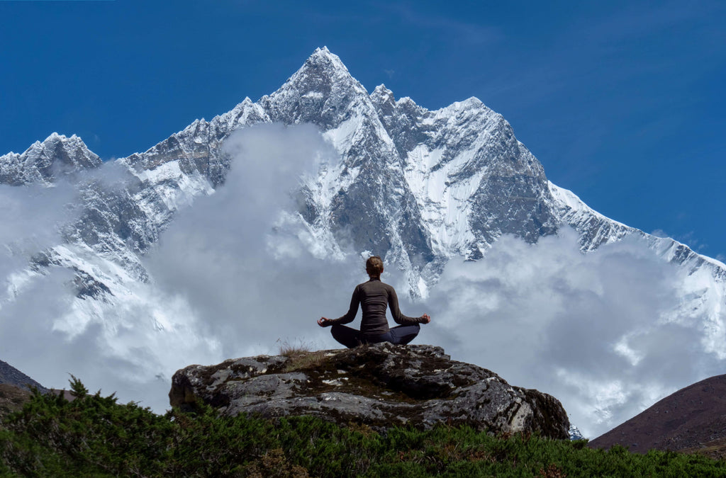 woman practicing deep breathing exercises on a mountain