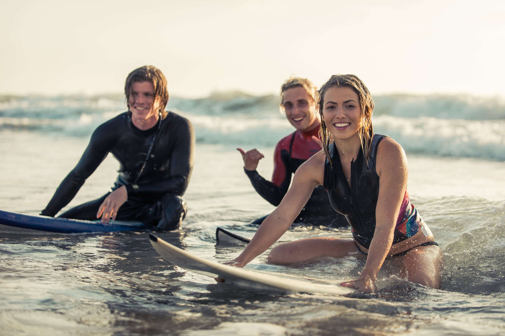 happy group of surfers on the beach