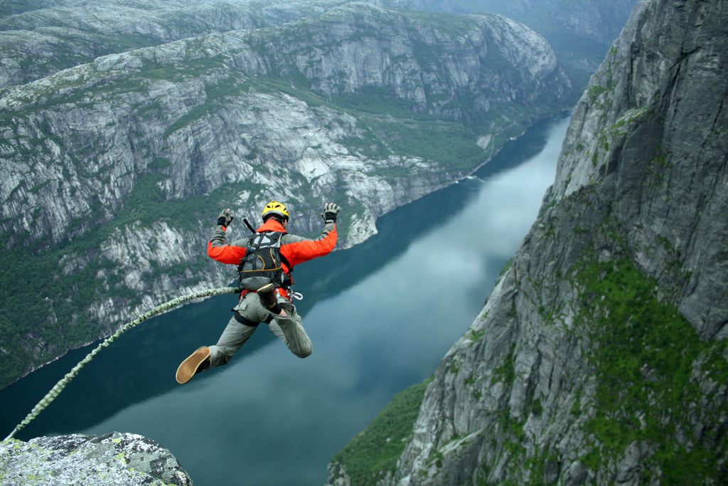 man rope jumping off a cliff