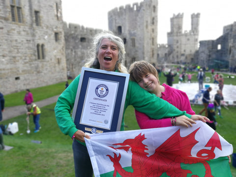 Guinness World Record breakers. Most giant bubbles made using giant rope, or tri-string and Most giant bubbles made using a garland, or multi-loop. Caernarfon Castle, North Wales.  Paola Dyboski-Bryant and Ziggy Dyboski-Bryant are Record Breakers.  Dr Zigs World Record most giant bubbles. Guinness Certificate and Welsh Flag