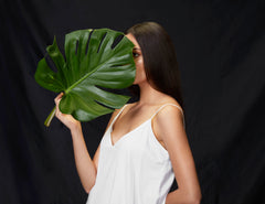Model holding leaf in hand wearing ALIGNe white skinny strap dress