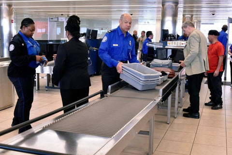TSA workers moving items through security