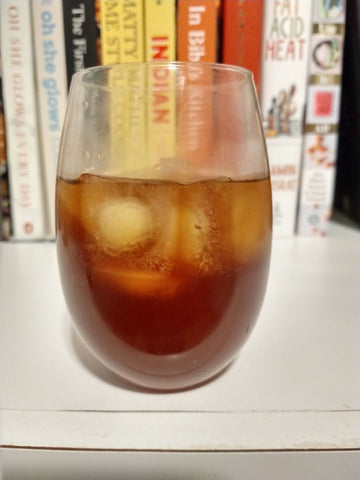 A glass of iced cold brew coffee sits on a shelf in front of a collection of cook books
