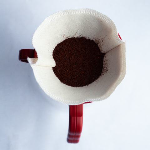 Birds eye view of a dry pour over dripper with coffee grinds inside sitting atop a red mug.