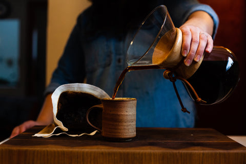 A person is pouring coffee from a Chemex into a ceramic mug. A cloth filter is in the background displaying the used coffee grinds.
