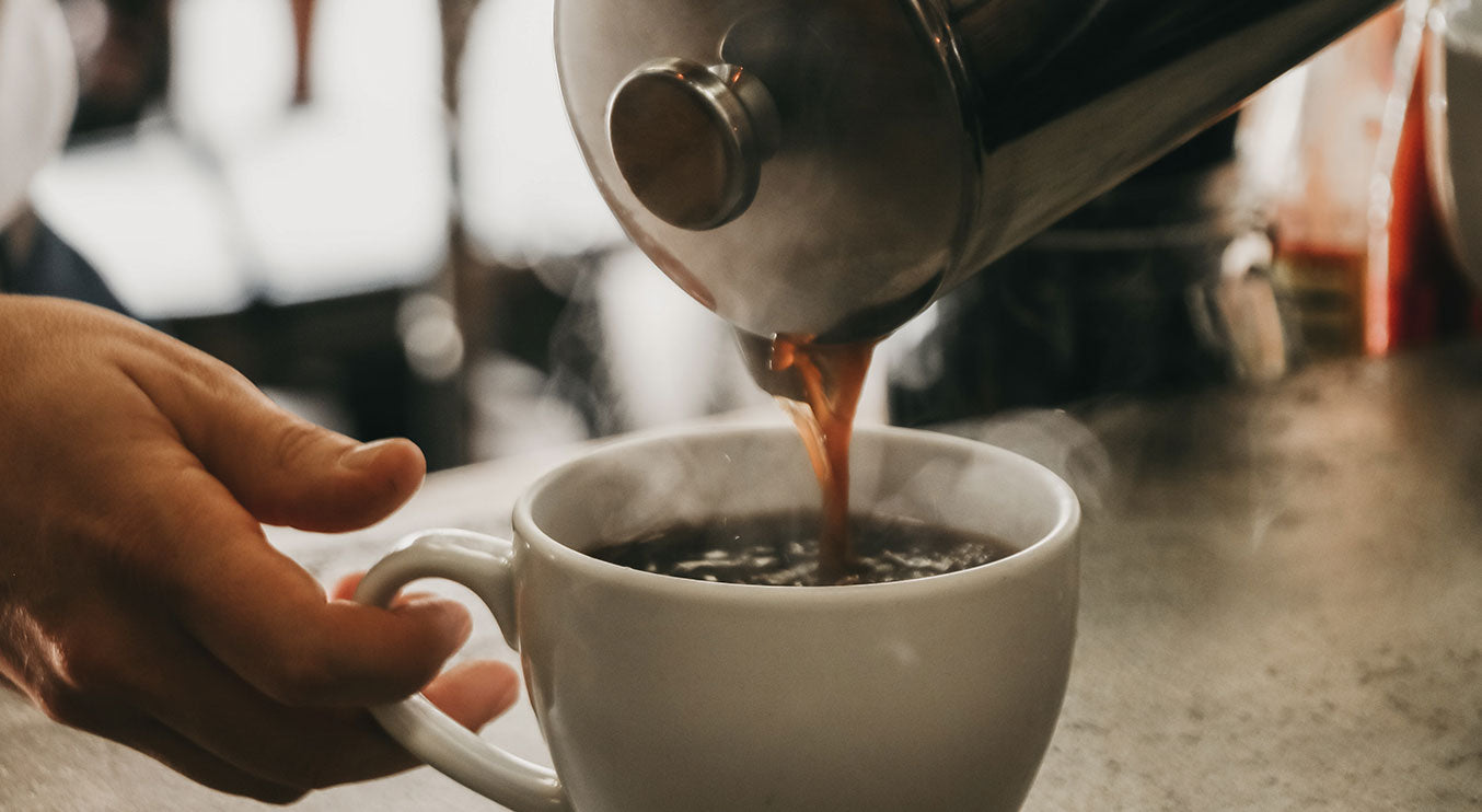 Photograph of coffee being poured from a french press.
