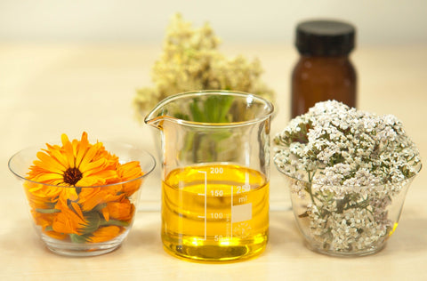 Essential oils and flowers in beakers