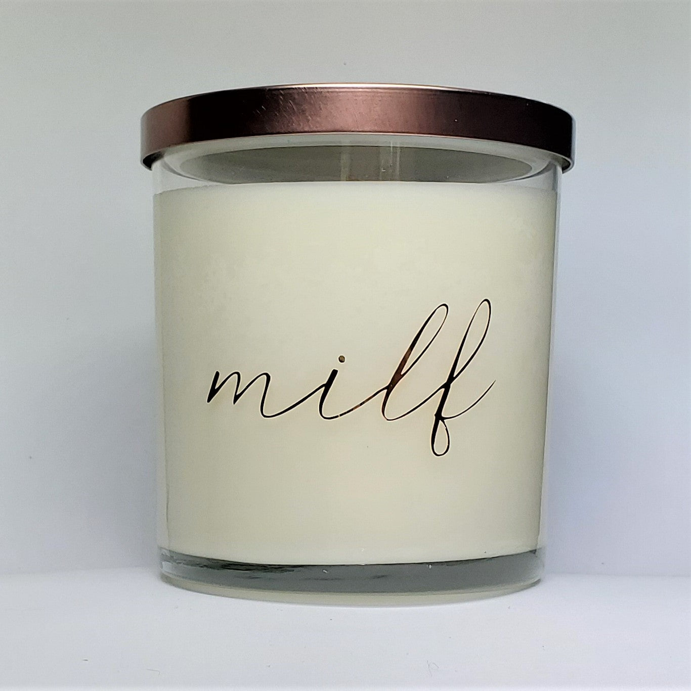 Milf candle, sexy scented candle in amber noir scented soy wax. Glass jar, bronze lid, front view.