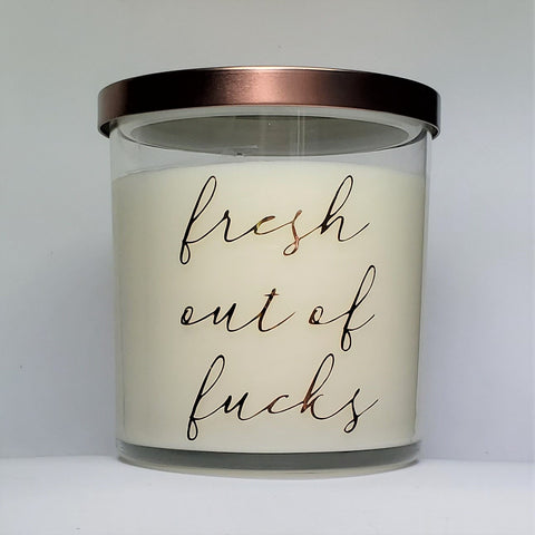 Fresh Out of Fucks candle, front view. Tangerine and mango scented soy candle, glass jar, bronze lid.