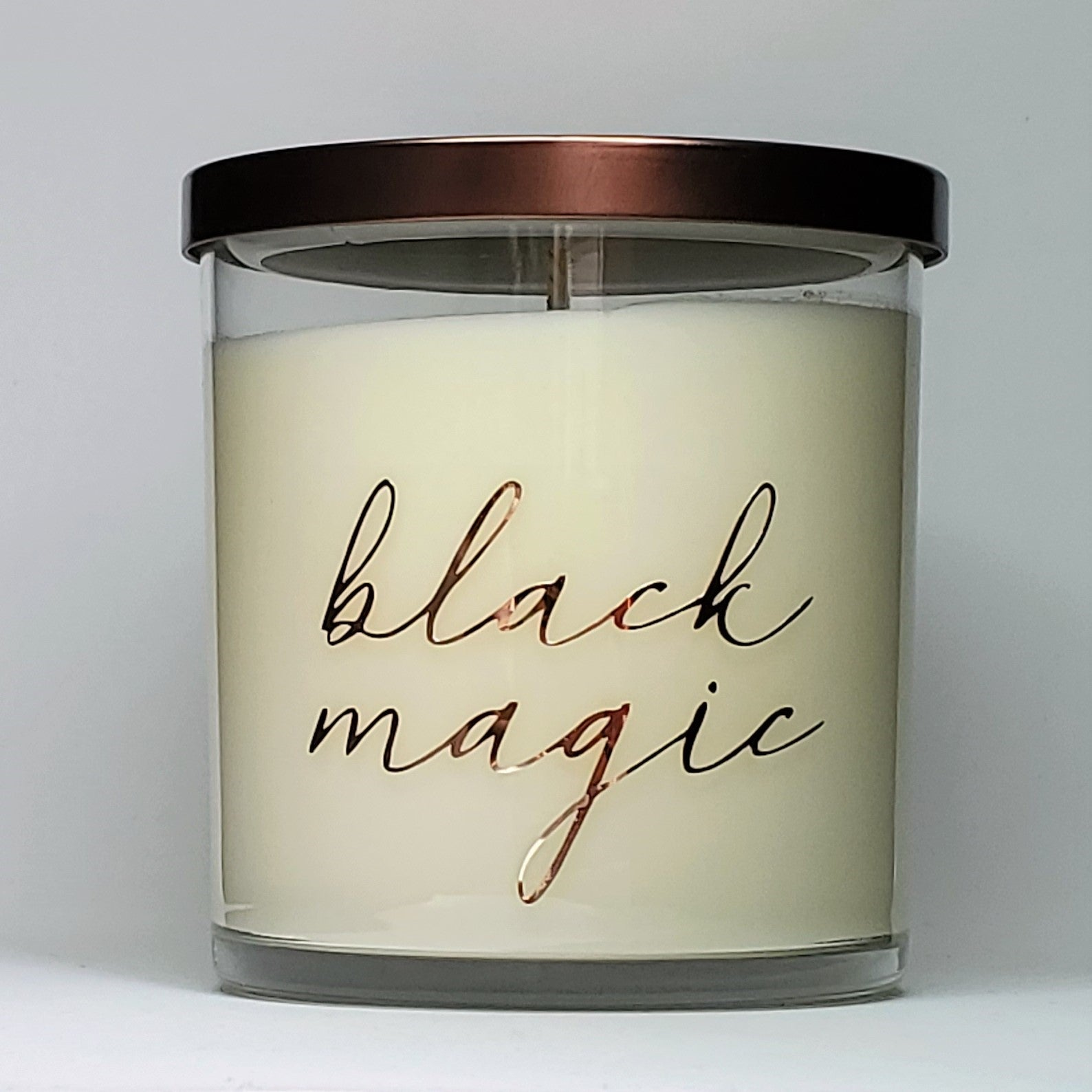 Black Magic scented soy candle. Rose, greenery, amaryllis, nag champa, incense, chardonnay scents. Front view of glass jar with bronze lid. Halloween themed collection, special edition candle.