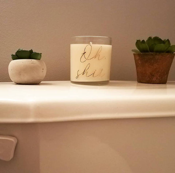 Oh shit candle, odor eliminator candle for bathrooms. Glass jar, bronze lid, front view, styled shot in a bathroom between two succulents.