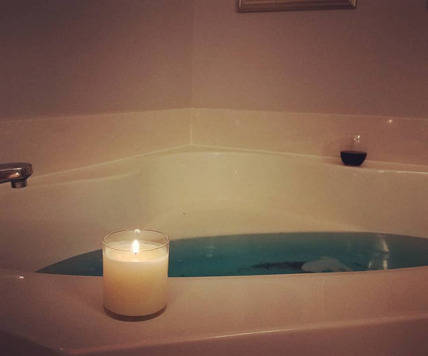 Queen candle, caramelized pralines baked goods scented soy wax candle, glass jar, bronze lid, styled next to a bathtub with blue water.