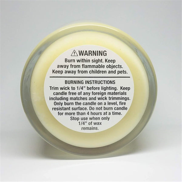 Basic Bitch candle, vanilla scented, bottom view of candle warning label. Glass jar, bronze lid.