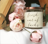 Fresh Out of Fucks candle posed in front of wooden triangle shelf with roses, peonies, and ranunculus. Tangerine and mango scented soy candle in glass jar with bronze lid.
