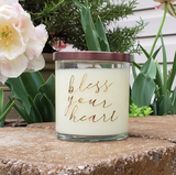 Styled image of Bless Your Heart candle in front of blooming tulips in springtime, outdoors. Front porch styled shot of honeysuckle jasmine candle in glass jar with bronze lid.