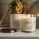 Classy AF candle styled in front of house plant, burning with lid off. Soy candle in glass jar with bronze lid. Luxury linen scent, like fresh laundry for home fragrance.