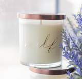 Milf candle, sexy scented candle in amber noir scented soy wax. Glass jar, bronze lid, posed next to lavender sprigs in a window.