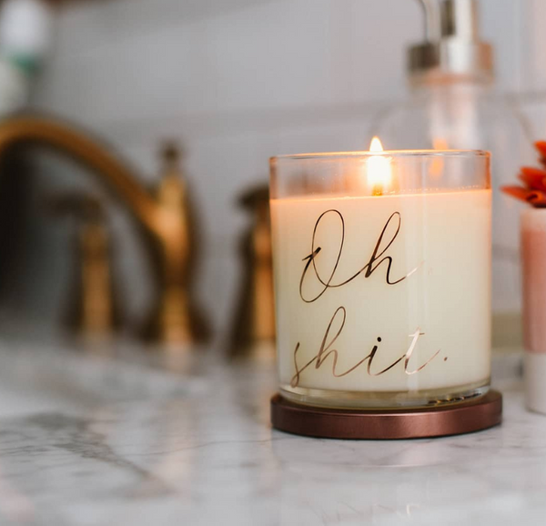 Oh shit candle, odor eliminator candle for bathrooms. Glass jar, bronze lid, styled shot in bathroom with bronze fixtures and lit.