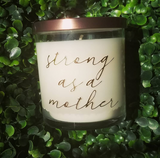 Strong as a mother candle, unscented candle, chemotherapy or childbirth gift, soy wax with no fragrance. Glass jar, bronze lid, front view, posed in front of a boxwood leaf background