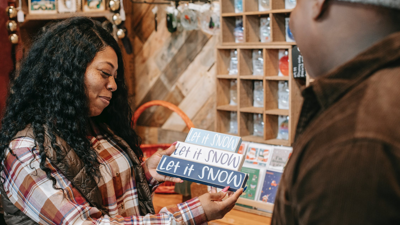Black owned businesses to shop: black woman looking at Christmas sign