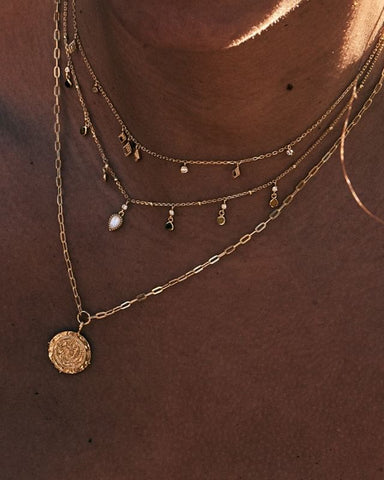 Layered necklaces with a coin necklace to anchor