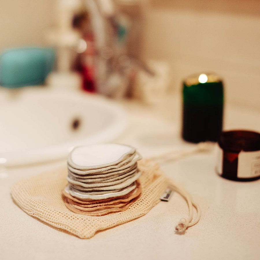 Bamboo makeup remover pads in atmospheric bathroom setting.