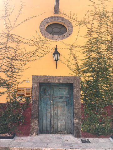yellow_stucco_window_oval_blue_doors_hacienda_architecture_san miguel_mexico
