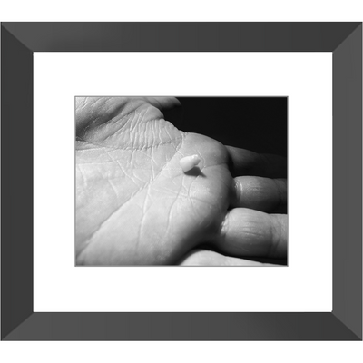 Meghan Nathanson Artistry black and white photo of a child's hand holding their first tooth 8x10 framed print