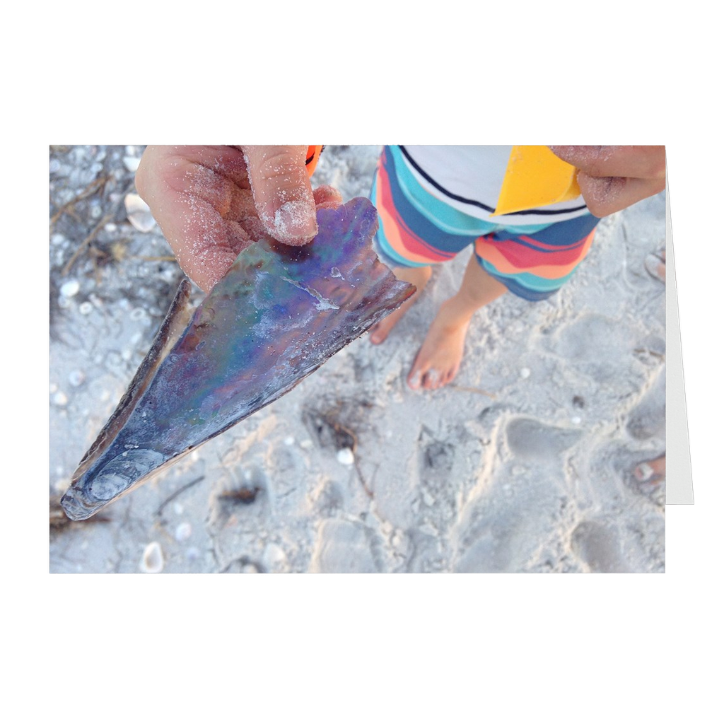 Meghan Nathanson Artistry color photo of child's hands holding a shell on the beach on folded greeting card