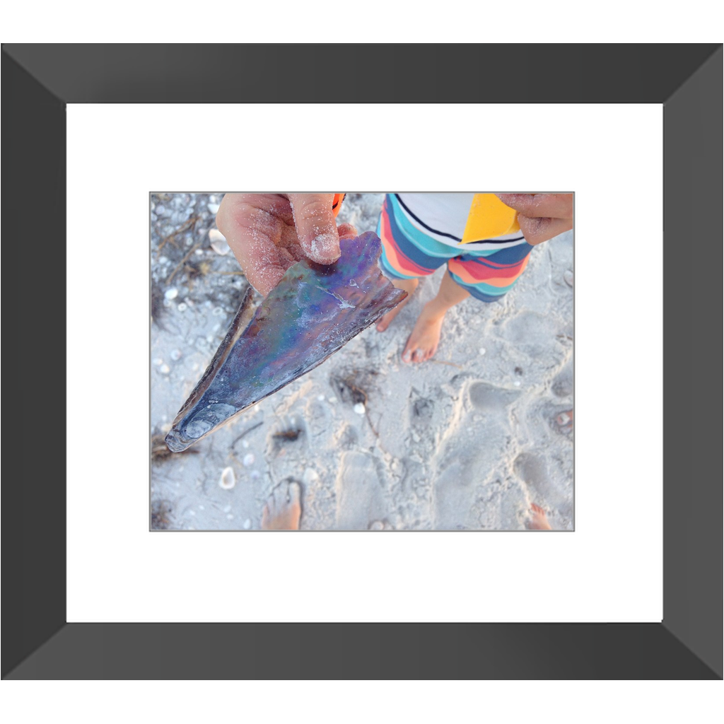 Meghan Nathanson Artistry color photo of child's hands holding a shell on the beach framed print