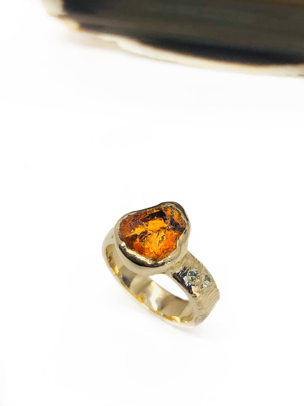 This one of a kind ring was handmade by our goldsmith and designer, Nell Henry, and showcases a brilliant 6 carat uncut Spessartite Tangerine Garnet. Two mint Beryls have been flush set on one side of the ring.   The 14k Yellow Gold shank has been lightly textured to resemble blades of grass by hand.